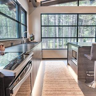 Idee per una piccola cucina moderna con lavello sottopiano, ante lisce, ante in legno bruno, top in granito, paraspruzzi grigio, paraspruzzi con piastrelle in pietra, elettrodomestici in acciaio inossidabile, pavimento in gres porcellanato, isola e pavimento nero