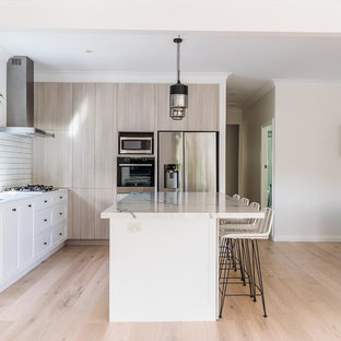 Mid-sized contemporary l-shaped open plan kitchen in Sydney with a double-bowl sink, quartz benchtops, white splashback, subway tile splashback, black appliances, light hardwood floors, with island, flat-panel cabinets, beige cabinets, beige floor and white benchtop.