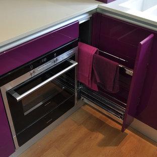 Immagine di una cucina design di medie dimensioni con lavello da incasso, ante lisce, ante viola, top in quarzite, paraspruzzi con lastra di vetro, elettrodomestici neri, parquet chiaro, penisola, pavimento marrone e top bianco