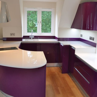 Inspiration for a mid-sized contemporary u-shaped open plan kitchen in Kent with a drop-in sink, flat-panel cabinets, purple cabinets, quartzite benchtops, glass sheet splashback, black appliances, light hardwood floors, a peninsula, brown floor and white benchtop.