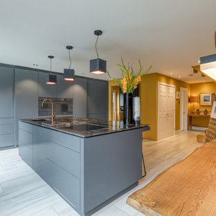 Photo of a large contemporary l-shaped open plan kitchen in Hertfordshire with a drop-in sink, louvered cabinets, grey cabinets, granite benchtops, panelled appliances, with island and black benchtop.