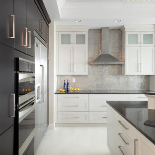This is an example of a mid-sized beach style l-shaped open plan kitchen in Miami with recessed-panel cabinets, white cabinets, mosaic tile splashback, stainless steel appliances, with island, quartz benchtops, metallic splashback, porcelain floors and white floor.