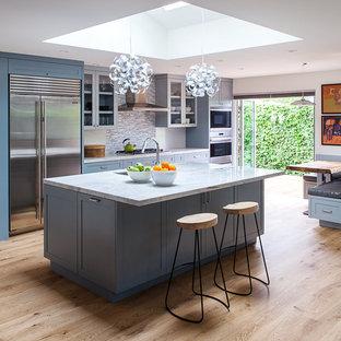 Cette image montre une très grande cuisine ouverte linéaire minimaliste avec un évier encastré, un placard à porte shaker, des portes de placard bleues, un plan de travail en quartz, une crédence multicolore, une crédence en carreau de porcelaine, un électroménager en acier inoxydable, un sol en bois brun et un îlot central.