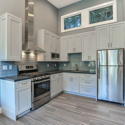 Inspiration for a small modern l-shaped gray floor open concept kitchen remodel in San Francisco with an undermount sink, shaker cabinets, white cabinets, gray backsplash, subway tile backsplash, stainless steel appliances, no island and black countertops