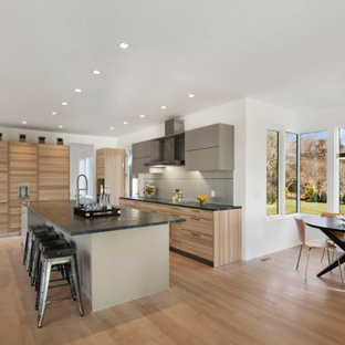 Contemporary kitchen inspiration - Example of a trendy l-shaped medium tone wood floor and brown floor kitchen design in New York with flat-panel cabinets, light wood cabinets, stainless steel appliances and an island