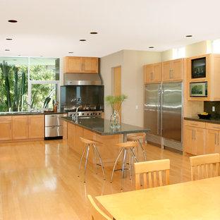 Cette image montre une cuisine américaine traditionnelle en U avec un placard à porte shaker, des portes de placard en bois clair, une crédence grise, une crédence en dalle de pierre, un électroménager en acier inoxydable et un plan de travail vert.