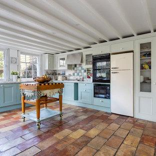 ロンドンの中サイズのシャビーシック調のおしゃれなキッチン (落し込みパネル扉のキャビネット、青いキャビネット、大理石カウンター、マルチカラーのキッチンパネル、モザイクタイルのキッチンパネル、パネルと同色の調理設備、テラコッタタイルの床、茶色い床) の写真