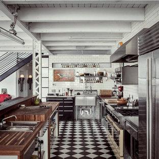 Idéer för att renovera ett industriellt brun brunt l-kök, med en nedsänkt diskho, släta luckor, svarta skåp, träbänkskiva, vitt stänkskydd, stänkskydd i tunnelbanekakel, rostfria vitvaror, en köksö och flerfärgat golv