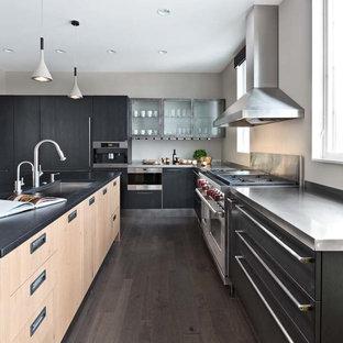 Modelo de cocina en L, actual, grande, con fregadero bajoencimera, armarios con paneles lisos, puertas de armario negras, encimera de cuarzo compacto, electrodomésticos con paneles, una isla y suelo de madera oscura