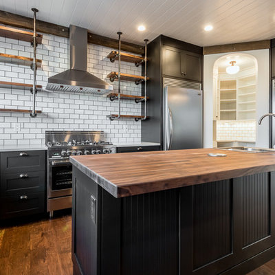Inspiration for a large industrial u-shaped medium tone wood floor and brown floor kitchen remodel in Chicago with shaker cabinets, black cabinets, wood countertops, white backsplash, subway tile backsplash, stainless steel appliances, an island and a farmhouse sink