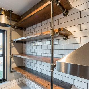 シカゴの大きいインダストリアルスタイルのおしゃれなキッチン (エプロンフロントシンク、シェーカースタイル扉のキャビネット、黒いキャビネット、木材カウンター、白いキッチンパネル、サブウェイタイルのキッチンパネル、シルバーの調理設備の、無垢フローリング) の写真