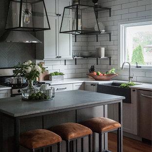 シカゴの中サイズのインダストリアルスタイルのおしゃれなキッチン (エプロンフロントシンク、シェーカースタイル扉のキャビネット、グレーのキャビネット、クオーツストーンカウンター、白いキッチンパネル、セラミックタイルのキッチンパネル、シルバーの調理設備の、淡色無垢フローリング、ベージュの床、グレーのキッチンカウンター) の写真