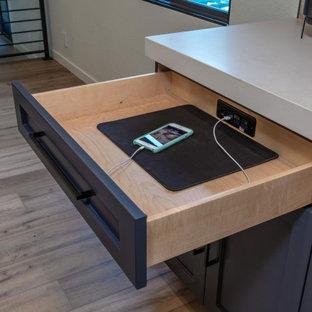 Inspiration för stora industriella svart kök, med en undermonterad diskho, skåp i shakerstil, svarta skåp, granitbänkskiva, stänkskydd i sten, rostfria vitvaror, laminatgolv, en köksö och brunt golv