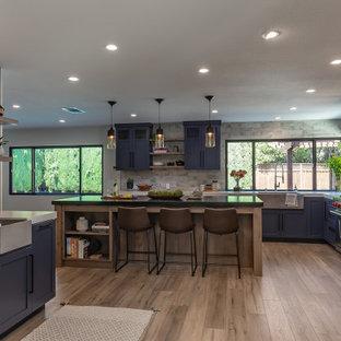 サンフランシスコの大きいインダストリアルスタイルのおしゃれなキッチン (アンダーカウンターシンク、シェーカースタイル扉のキャビネット、黒いキャビネット、御影石カウンター、石スラブのキッチンパネル、シルバーの調理設備の、ラミネートの床、茶色い床、黒いキッチンカウンター) の写真