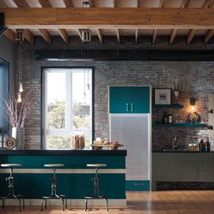 シカゴの中くらいのインダストリアルスタイルのおしゃれなキッチン (フラットパネル扉のキャビネット、ターコイズのキャビネット、レンガのキッチンパネル、シルバーの調理設備) の写真