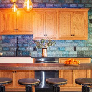 Ejemplo de cocina rústica, de tamaño medio, con fregadero sobremueble, armarios estilo shaker, puertas de armario de madera oscura, encimera de granito, salpicadero azul, salpicadero de azulejos de cerámica, electrodomésticos de acero inoxidable, suelo gris y encimeras negras