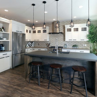 Foto de cocina en L, urbana, con fregadero de doble seno, armarios con paneles empotrados, puertas de armario blancas, encimera de cemento, electrodomésticos de acero inoxidable, suelo de madera oscura y una isla