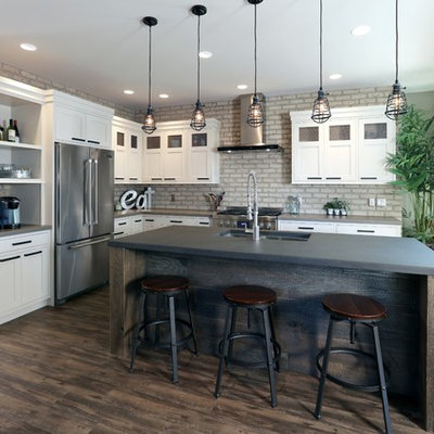Urban l-shaped dark wood floor kitchen photo in Grand Rapids with a double-bowl sink, recessed-panel cabinets, white cabinets, concrete countertops, stainless steel appliances and an island