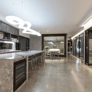 ブリスベンの中くらいのインダストリアルスタイルのおしゃれなキッチン (アンダーカウンターシンク、インセット扉のキャビネット、中間色木目調キャビネット、大理石カウンター、ガラス板のキッチンパネル、黒い調理設備、コンクリートの床、ベージュの床) の写真