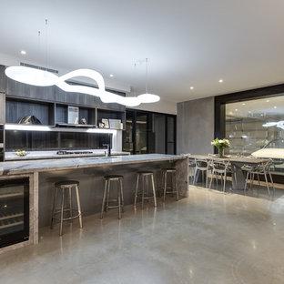 ブリスベンの中サイズのインダストリアルスタイルのおしゃれなキッチン (アンダーカウンターシンク、インセット扉のキャビネット、中間色木目調キャビネット、大理石カウンター、ガラス板のキッチンパネル、黒い調理設備、コンクリートの床、ベージュの床) の写真