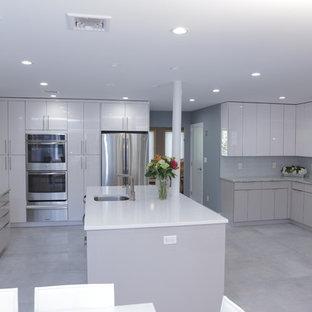 ニューヨークの大きいモダンスタイルのおしゃれなキッチン (ドロップインシンク、フラットパネル扉のキャビネット、白いキャビネット、再生ガラスカウンター、青いキッチンパネル、ガラス板のキッチンパネル、シルバーの調理設備の、コンクリートの床) の写真