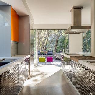 Modern inredning av ett kök, med rostfria vitvaror och orange skåp