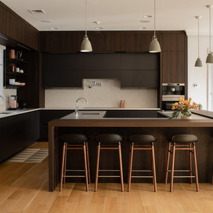 Contemporary kitchen designs - Trendy u-shaped medium tone wood floor and brown floor kitchen photo in New York with flat-panel cabinets, brown cabinets, beige backsplash, an island and brown countertops
