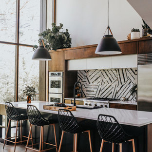 Contemporary kitchen ideas - Trendy galley light wood floor and beige floor kitchen photo in Seattle with an undermount sink, flat-panel cabinets, dark wood cabinets, multicolored backsplash, stainless steel appliances, an island and white countertops