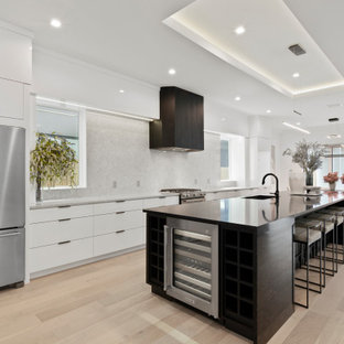 Inspiration for a contemporary galley kitchen in Orlando with an undermount sink, flat-panel cabinets, white cabinets, grey splashback, stainless steel appliances, light hardwood floors, with island, beige floor, black benchtop and recessed.