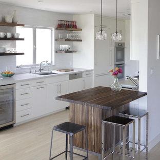 Cette photo montre une cuisine parallèle moderne avec un évier 1 bac, un placard sans porte, des portes de placard blanches, un électroménager encastrable, un plan de travail en quartz modifié et une crédence blanche.