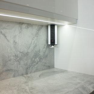 デンバーの中サイズのモダンスタイルのおしゃれなキッチン (アンダーカウンターシンク、フラットパネル扉のキャビネット、白いキャビネット、クオーツストーンカウンター、白いキッチンパネル、石スラブのキッチンパネル、シルバーの調理設備の、濃色無垢フローリング) の写真