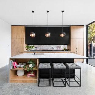 Ispirazione per una cucina parallela contemporanea con ante nere, top in quarzo composito, pavimento in cemento, isola, lavello sottopiano, ante lisce e elettrodomestici da incasso