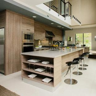 Offene, Zweizeilige Moderne Küche mit Unterbauwaschbecken, flächenbündigen Schrankfronten, orangefarbenen Schränken, Küchenrückwand in Grau, Küchengeräten aus Edelstahl, Kücheninsel, weißem Boden und brauner Arbeitsplatte in Los Angeles
