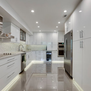 Modern kitchen ideas - Example of a minimalist kitchen design in DC Metro with an undermount sink, flat-panel cabinets, quartz countertops, glass tile backsplash and stainless steel appliances