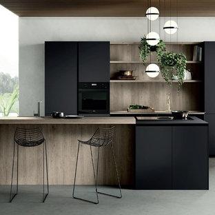 Imagen de cocina lineal, minimalista, de tamaño medio, abierta, con fregadero encastrado, armarios con paneles lisos, puertas de armario negras, encimera de madera, electrodomésticos negros, suelo de cemento, una isla, suelo gris y encimeras marrones