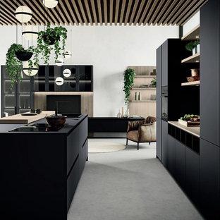 Пример оригинального дизайна: линейная кухня-гостиная среднего размера в стиле модернизм с накладной раковиной, плоскими фасадами, черными фасадами, деревянной столешницей, черной техникой, бетонным полом, островом, серым полом и коричневой столешницей