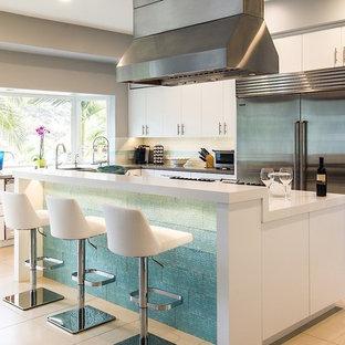 Große Moderne Wohnküche in L-Form mit Unterbauwaschbecken, flächenbündigen Schrankfronten, weißen Schränken, Mineralwerkstoff-Arbeitsplatte, Küchenrückwand in Weiß, Rückwand aus Metrofliesen, Küchengeräten aus Edelstahl, Keramikboden und Kücheninsel in Los Angeles