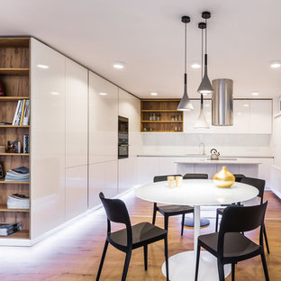 This is an example of a mid-sized contemporary l-shaped eat-in kitchen in Other with flat-panel cabinets, white cabinets, limestone benchtops, white splashback, stainless steel appliances, plywood floors, with island and brown floor.
