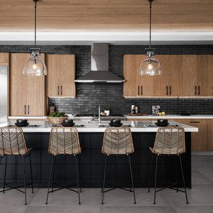 Стильный дизайн: угловая кухня-гостиная среднего размера в стиле модернизм с плоскими фасадами, мраморной столешницей, черным фартуком, фартуком из керамической плитки, техникой из нержавеющей стали, островом, серым полом, белой столешницей, накладной раковиной, светлыми деревянными фасадами и полом из цементной плитки - последний тренд