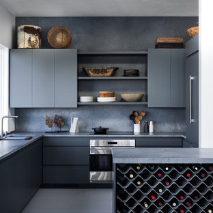 Inspiration for a modern u-shaped kitchen in New York with flat-panel cabinets, grey cabinets, concrete benchtops, grey splashback, stainless steel appliances, grey floor and grey benchtop.