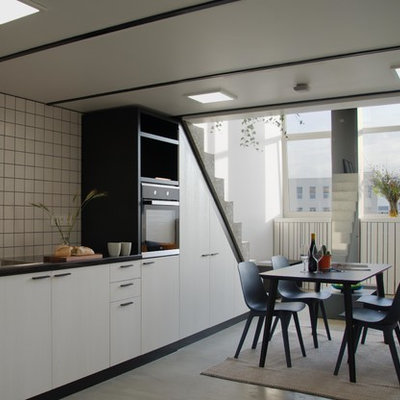 Example of a mid-sized minimalist single-wall concrete floor and gray floor open concept kitchen design in London with a drop-in sink, flat-panel cabinets, solid surface countertops, white backsplash, ceramic backsplash, black appliances, no island and black countertops