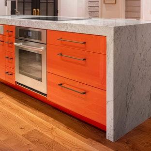 デンバーの中サイズのモダンスタイルのおしゃれなキッチン (アンダーカウンターシンク、フラットパネル扉のキャビネット、オレンジのキャビネット、大理石カウンター、シルバーの調理設備の、無垢フローリング) の写真