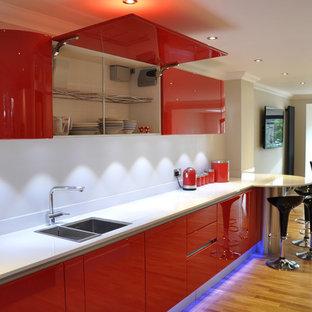 ケントの大きいコンテンポラリースタイルのおしゃれなキッチン (ドロップインシンク、フラットパネル扉のキャビネット、赤いキャビネット、珪岩カウンター、白いキッチンパネル、シルバーの調理設備の、無垢フローリング、茶色い床、白いキッチンカウンター) の写真