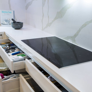 This is an example of an expansive contemporary u-shaped kitchen pantry in Brisbane with a single-bowl sink, flat-panel cabinets, white cabinets, engineered stone countertops, white splashback, stone slab splashback, stainless steel appliances, light hardwood flooring and an island.