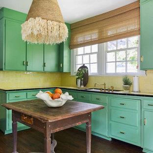 Immagine di una cucina tropicale con lavello sottopiano, ante lisce, ante verdi, top piastrellato, paraspruzzi giallo, parquet scuro, isola, pavimento marrone e top giallo