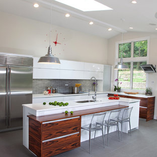Inspiration for a large contemporary eat-in kitchen in New York with flat-panel cabinets, white cabinets, stainless steel appliances, an undermount sink, quartz benchtops, beige splashback, glass tile splashback, porcelain floors and with island.