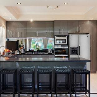 メルボルンの広いモダンスタイルのおしゃれなキッチン (ドロップインシンク、フラットパネル扉のキャビネット、グレーのキャビネット、クオーツストーンカウンター、メタリックのキッチンパネル、ガラス板のキッチンパネル、シルバーの調理設備、セラミックタイルの床) の写真