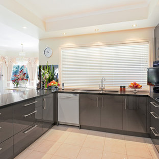 Example of a large minimalist u-shaped ceramic floor open concept kitchen design in Melbourne with a drop-in sink, flat-panel cabinets, gray cabinets, quartz countertops, metallic backsplash, glass sheet backsplash, stainless steel appliances and an island