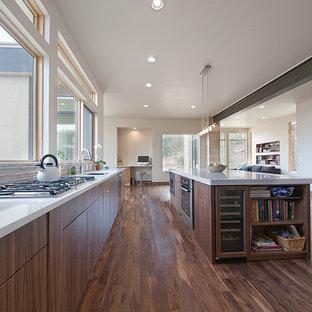 Imagen de cocina de galera, minimalista, abierta, con armarios con paneles lisos, puertas de armario de madera en tonos medios y salpicadero verde