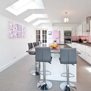 Moderne Küche in L-Form mit Unterbauwaschbecken, flächenbündigen Schrankfronten, weißen Schränken, Küchenrückwand in Rosa, Glasrückwand, bunten Elektrogeräten und Kücheninsel in Surrey